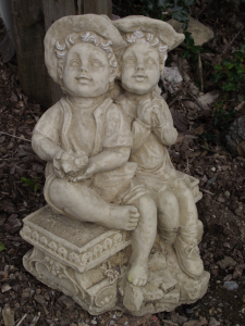 Stone Boy and Girl Sitting on a Bench