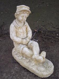 Stone Boy Statue Sitting in a Meadow